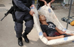 Rio police carry body of dead suspected drug dealer, image recreation.