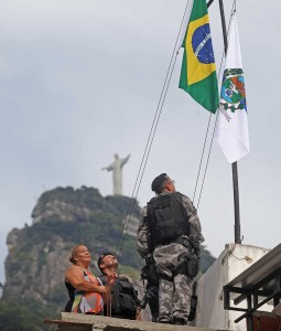 Brazil and Rio State flags are raised over the Cerro-Corá favela after the area in readied for the city's 33rd UPP, Rio de Janeiro, Brazil News