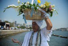 Brazil, Rio de Janeiro,Umbandista-religion members carry flowers to the sea to honor Godess of the Sea, Iemanjá,