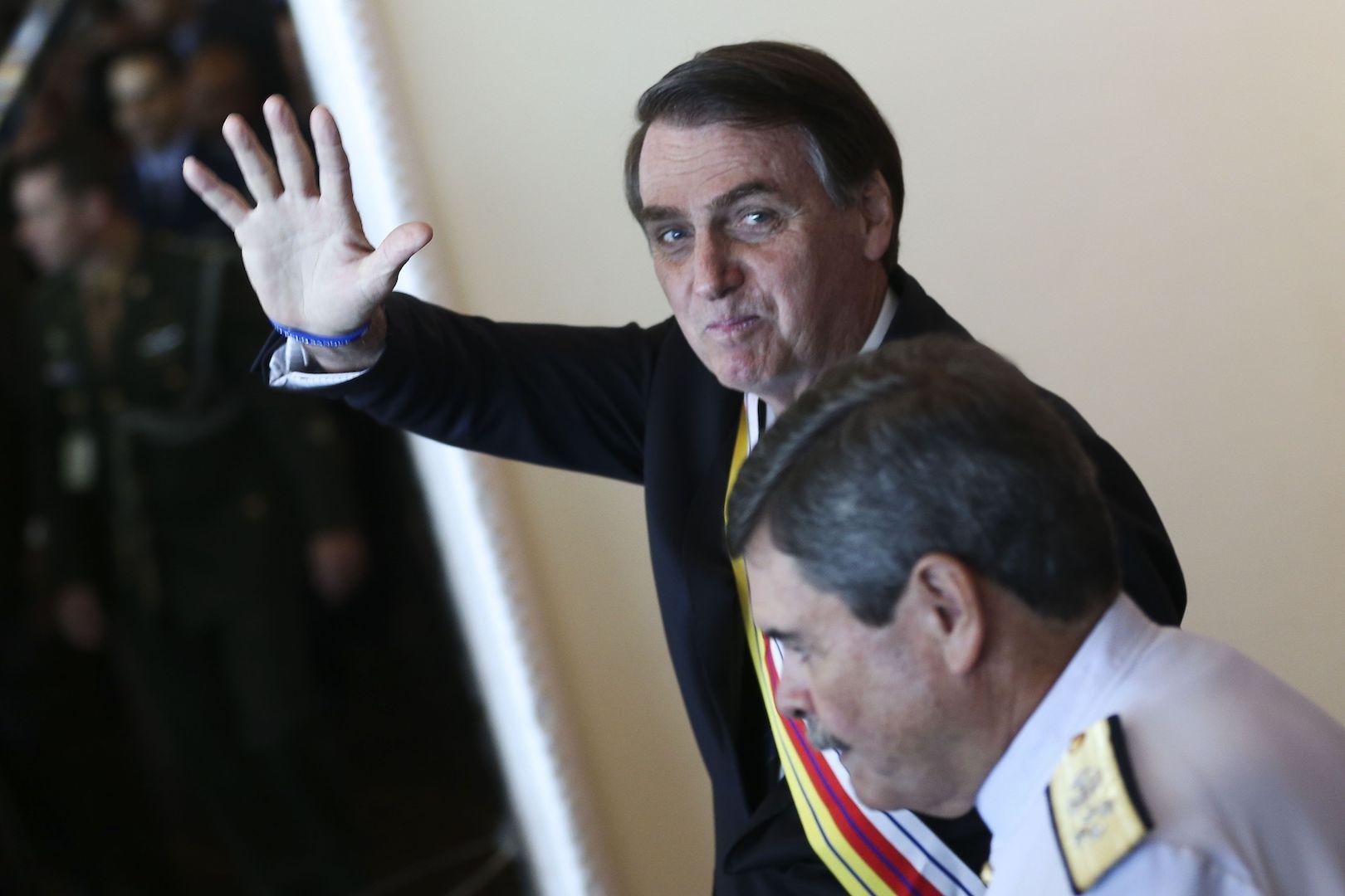Brazil,President Jair Bolsonaro waves to reporters after ceremony in Brasilia,